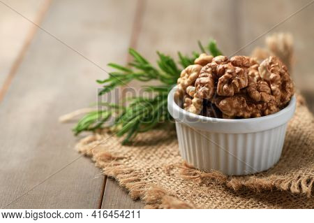 Walnut In White Cup On Wood Background. Healthy Nuts Concept. Walnuts Are An Excellent Source Of Ant