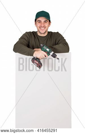 Friendly Maintenance Worker With A Screwdriver Or Electric Drill In His Hand, Stands Behind A White