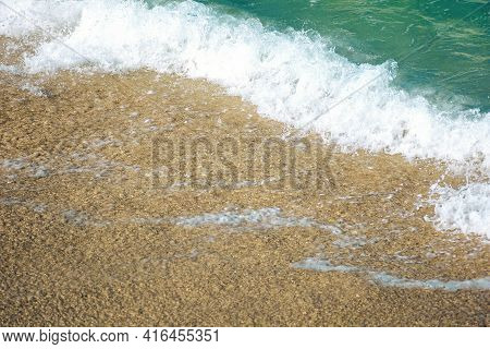 Close Up Texture Of The Sea Wave Rolling On To The Golden Sandy Beach. Abstract Nature Background On