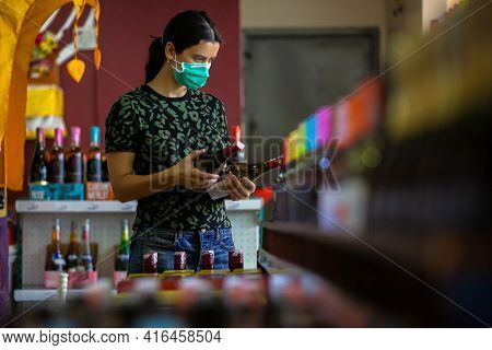 Young Woman Wears Medical Mask Against Coronavirus While Grocery Shopping In Supermarket- Health, Sa