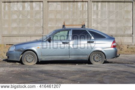 An Old Dented Silver-colored Car At A Gray Concrete Fence, Ulitsa Badaeva, St. Petersburg, Russia, A