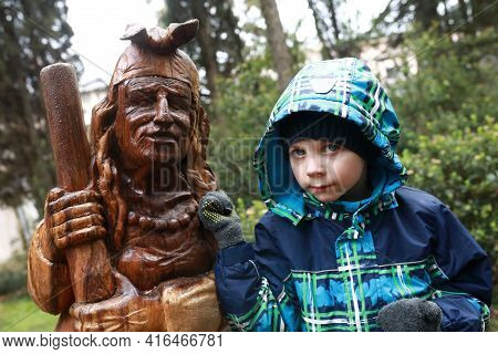 Child With Wooden Sculpture Of Baba Yaga