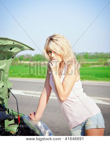 Blonde Girl Stands Near The Broken Car