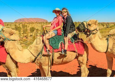 Uluru, Australia - Aug 2019:couple Camel Riding In Australian Desert Of Northern Territory With Ulur