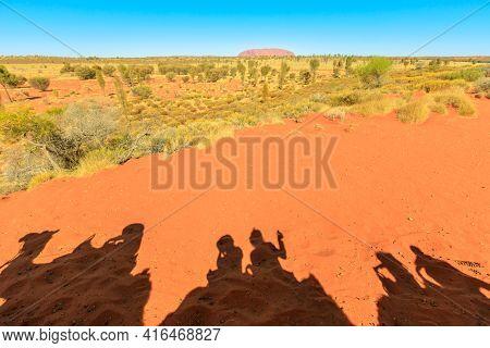 Uluru, Australia - Aug 2019:people Shadow Of Camel Riding In Australian Desert Of Northern Territory