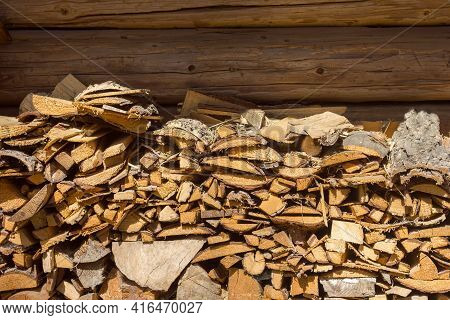 A Stack Of Firewood From Wooden Blocks For Kindling A Fire Lie Near A Wooden Wall Made Of Boards, Co