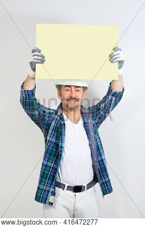 A Builder In A Safety Helmet Lifted An Empty Workpiece To The Top, A Mock-up