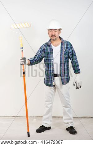 Builder Repairman Holding A Long Paint Roller In His Hand On A White Wall Background