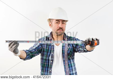 A Builder In A Protective Helmet Holds A Construction Tape Measure In His Hands During Home Renovati