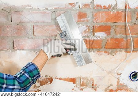 Construction Worker Plastering A Brick Wall With A Spatula During The Renovation Of A House, Apartme