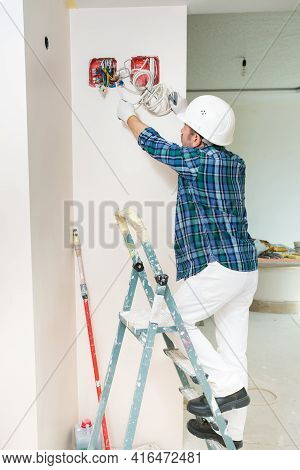 Electrician Construction Worker In A Protective Helmet Assembles A Junction Box With Voltage Wires W