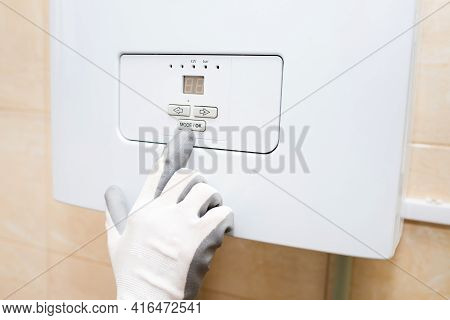 Construction Worker Plumbing Enters The Water Heater, Boiler Close-up
