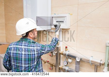 The Work Of A Plumber In A Protective Helmet, Autonomous Heating Of The House, Water Heating