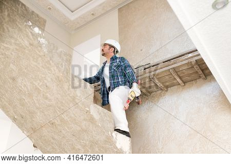 Builder, Repairman In A Protective Helmet With A Tool, On A Concrete Staircase During Construction,