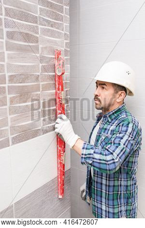 Builder Repairman Checks The Flatness Of The Laid Tiles In The Bathroom