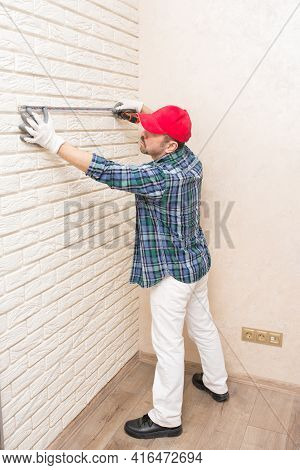 A Builder-repairman, Standing, Measures The Length Of A Wall Made Of Decorative Bricks With A Constr