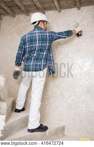Builder-repairman Plasterer, In A Protective Helmet, When Repairing, Applies Decorative Plaster, A P