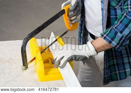 A Builder In A Protective Helmet Cuts A Baguette With A Hacksaw During House Renovation, Close-up