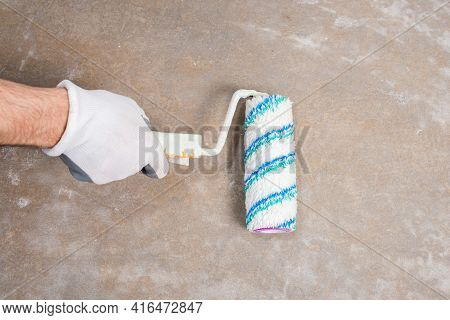 Builder Repairman In Protective Gloves Priming Concrete Floor With Paint Roller, Construction Mockup