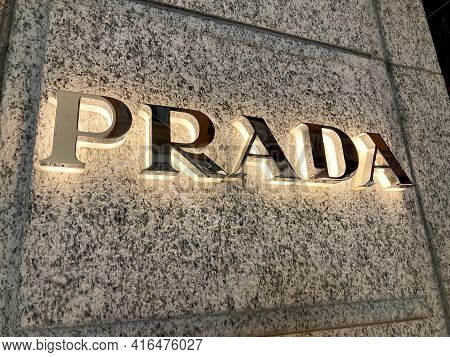 Lugano, Ticino, Switzerland - 10th March 2021 : Illuminated Prada Sign Hanging On The Store Wall In