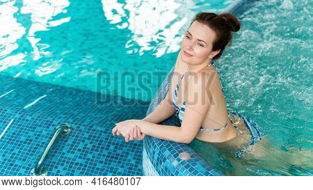 A Pretty Adult Girl With Naked Skin Relaxes In A Pool With Hydromassage In The Aqua Zone Of The Spa