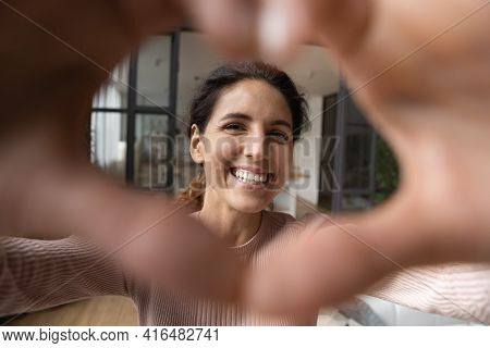 Hispanic Female Looking At Camera Through Heart Of Joined Fingers.