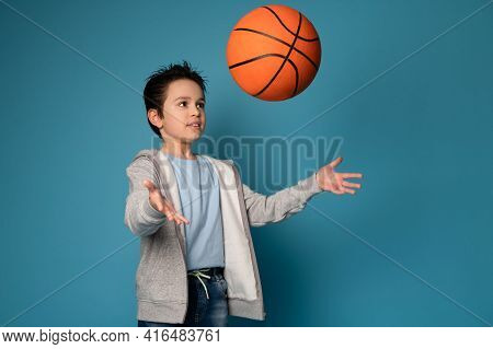 Adorable Boy Child Throwing A Ball While Playing Basketball. Isolated Portrait Of A Young Basketball