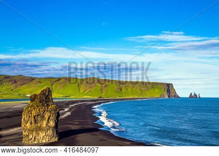Cape Dyrholaey. The southern edge of Iceland. Beach with black volcanic ash Reinisfjara. Giant lonely rock - Palm on a black volcanic sand beach