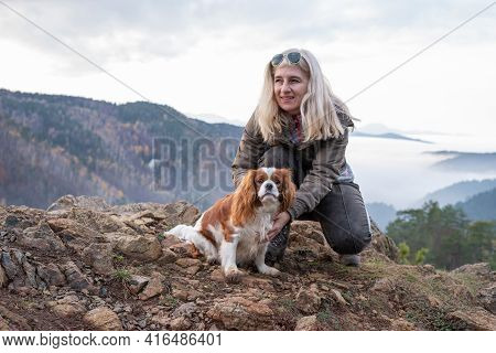 Blond Woman And Her Cavalier King Charles Spaniel On A Mountain Top On A Hazy Day