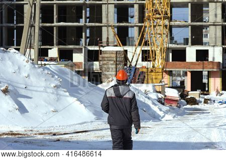 A Builder In Uniform And An Orange Construction Helmet Goes To A Construction Site In Winter