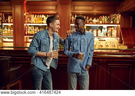 Two male friends poses with glasses of beer in bar