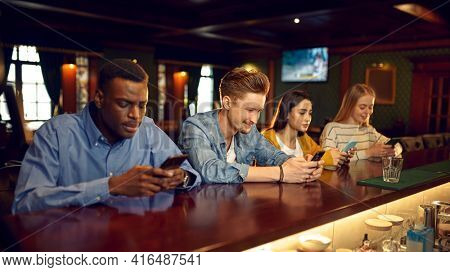 Friends using mobile phones at the counter in bar