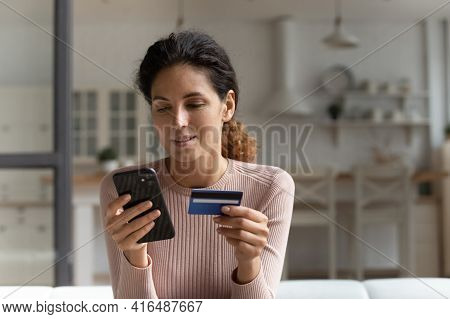 Millennial Latina Female Using Telephone To Make Easy Payment Online