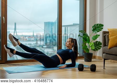 Slender brunette woman practices abdominal exercises on blue mat by pot plant and panoramic window city view outside in room