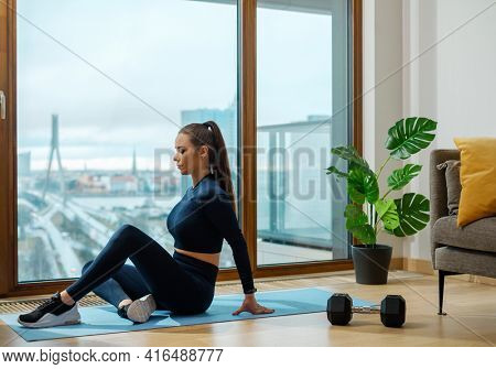 Slender brunette with ponytail in turquoise tracksuit practices yoga position on blue mat near panoramic window on balcony