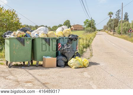 Campos, Spain; April 10 2021: Three Garbage Containers Full Of Garbage Bags Inside And With More Gar