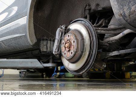 A Modern Car On A Lift In A Car Service With A Wheel Removed. Brake Disc, Brake Caliper. Car Service