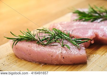 Pieces Of Raw Turkey Steaks With Spices And Herbs Rosemary, Salt And Pepper On Wooden Background. Co