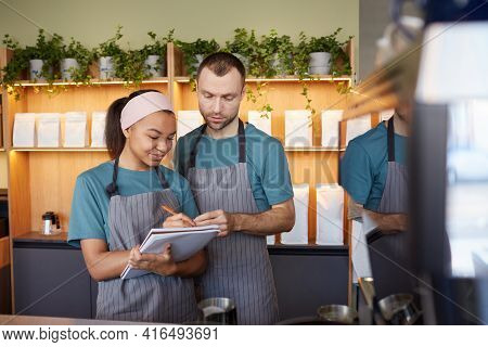 Waist Up Portrait Of Two Young Waiters Wearing Aprons And Holding Clipboard While Doing Inventory In