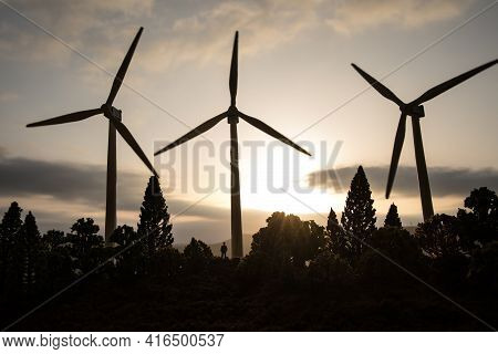 Concept Idea Eco Power Energy. Wind Turbine On Hill With Sunset. Wind Turbine Producing Alternative