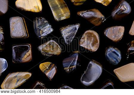 Tiger's Eye Rare Jewel Texture On Black Background. Sparse Mineral Pebbles Background.