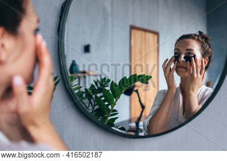 Young Woman Applies Patches Under Her Eyes.