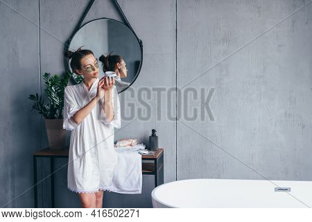 Woman Holds A Jar Of Eye Patches And Reads How To Use