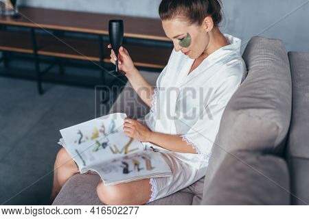 Woman At Home In A Nightgown With A Magazine, A Glass And Patches On Her Face