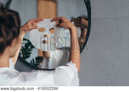 Woman With Sheet Mask In Her Hands In The Bathroom Before Applying It To Her Face