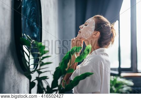 Woman In The Bathroom Taking Care Of Her Facial Skin By Applying A Mask To Her Face