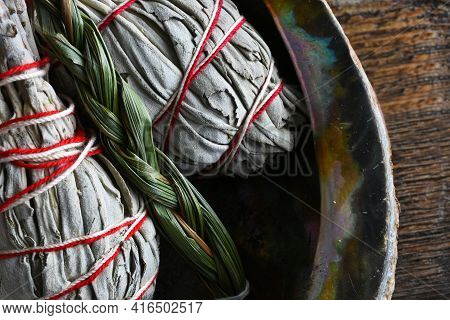 A Close Up Image Of White Sage Smudge Sticks And Sweet Grass Smudge Sticks In An Abalone Shell.