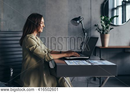 Woman Works At Home Sitting At Her Desk With Her Laptop
