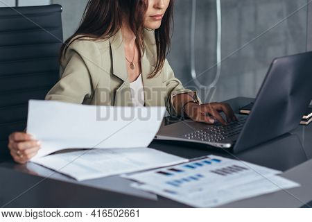 Woman Works With Documents While Sitting At Her Desk.