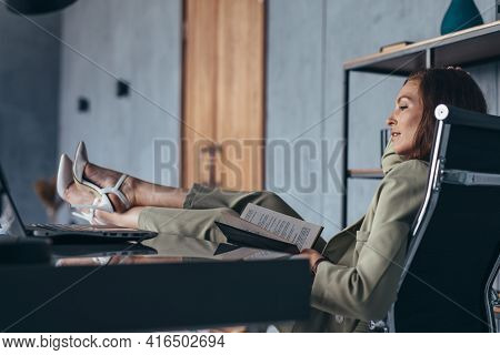 Woman Sits With Her Feet Up On Her Desk